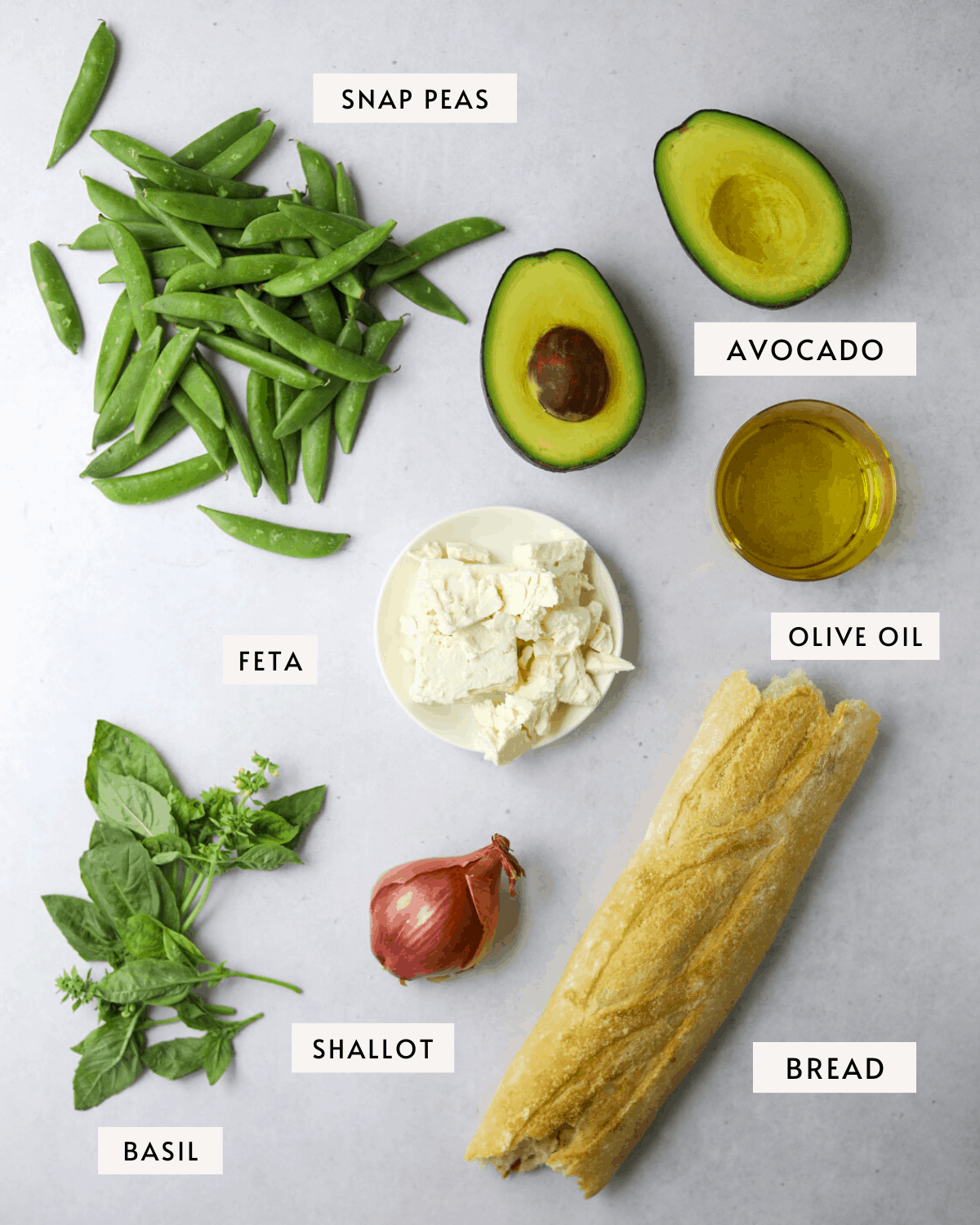 recipe ingredients on a blue background; a loaf of bread, olive oil, avocado, basil, shallot, snap peas and feta cheese