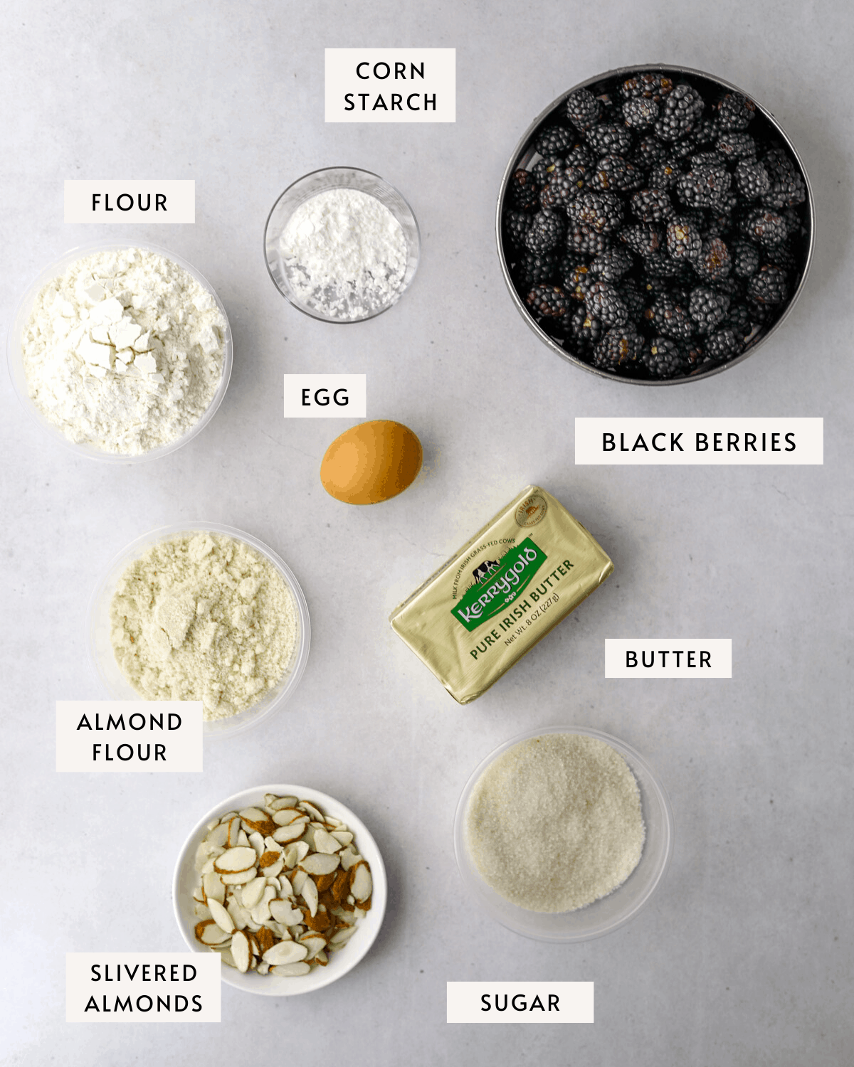 recipe ingredients measured into bowls: black berries, egg, butter, corn starch, flour and slivered almonds