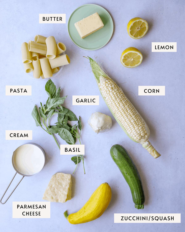 recipe ingredients individually portioned, an ear of corn, a lemon, dried rigatoni pasta, fresh basil, garlic, butte, zucchini and summer squash