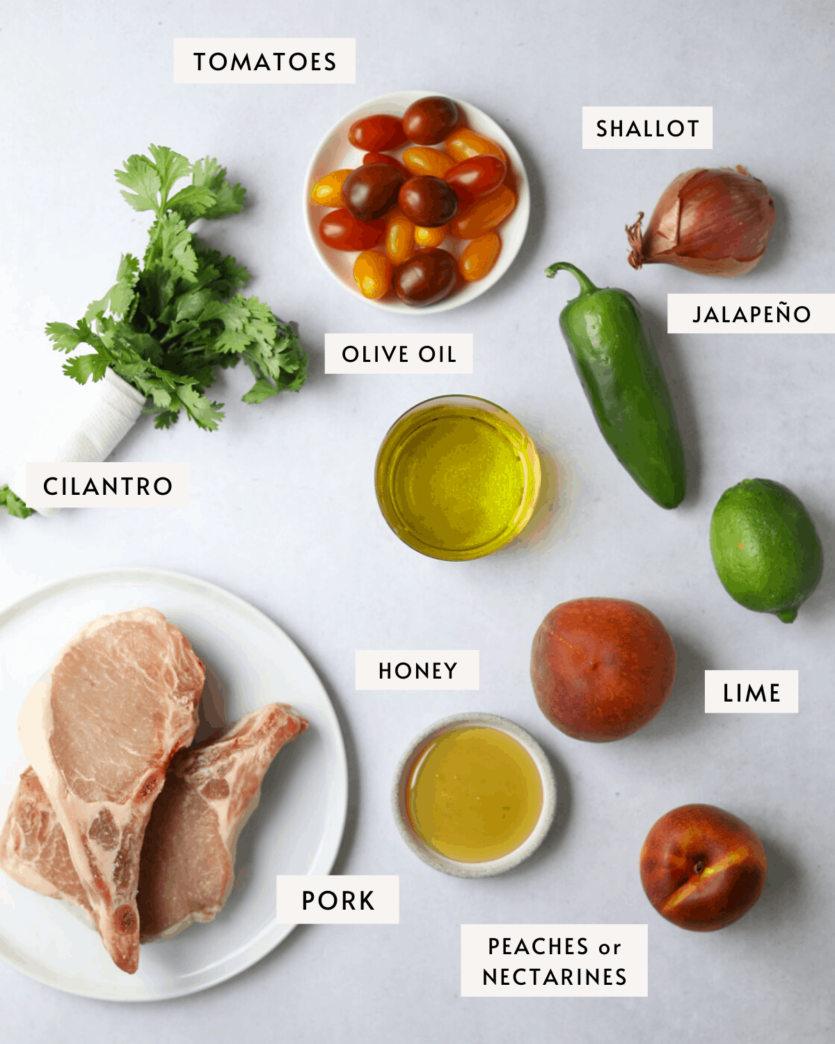 recipe ingredients, a plate of raw pork chops, a jalapeño, olive oil, honey, peaches, nectarines, shallot and cilantro