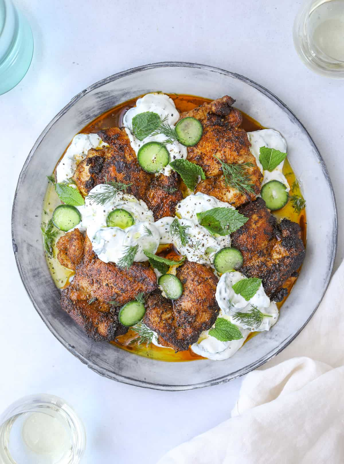 a plate of smokey paprika chicken with dollops of cucumber tzatziki, fresh mint and cucumber slices on a blue background with a white linen napkin
