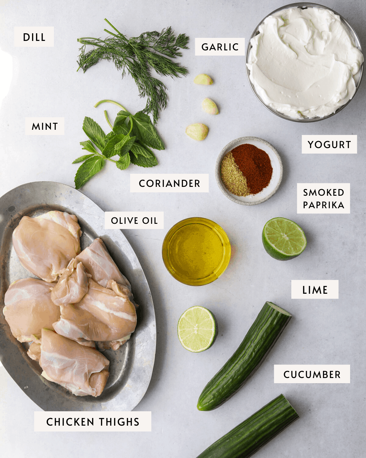 recipe ingredients individually portioned, a bowl of yogurt, chicken thighs, fresh herbs and spices, olive oil, lime juice and garlic