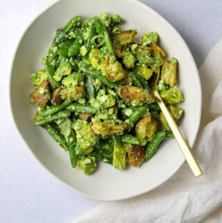 a white oval bowl filled with bright green avocado panzanella salad with a gold spoon and an off white tea towel.