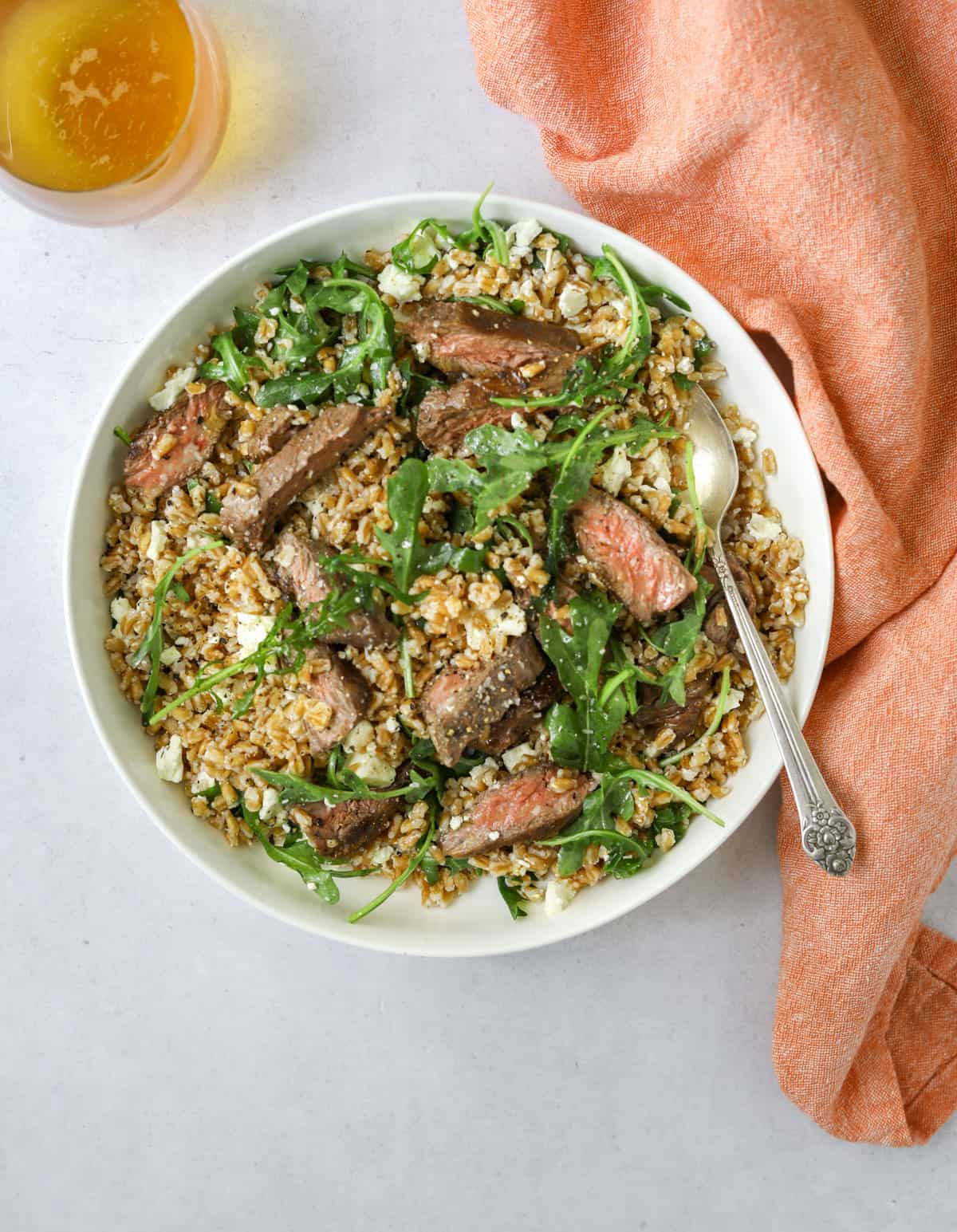 farro salad in a white bowl with a silver spoon and a pink tea towel and a glass of wine on a blue background