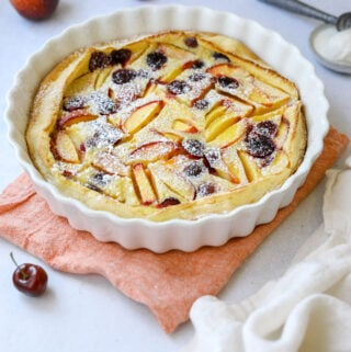 a white fluted baking dish filled with stone fruit clafoutis dusted in powdered sugar, surrounded by peaches, cherries and a scoop of vanilla ice cream