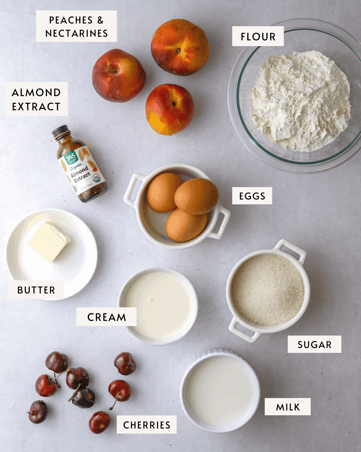 stone fruit clafoutis ingredients individually portioned; a bowl of flour, three peaches, brown eggs, butter, cream, sugar, almond extract
