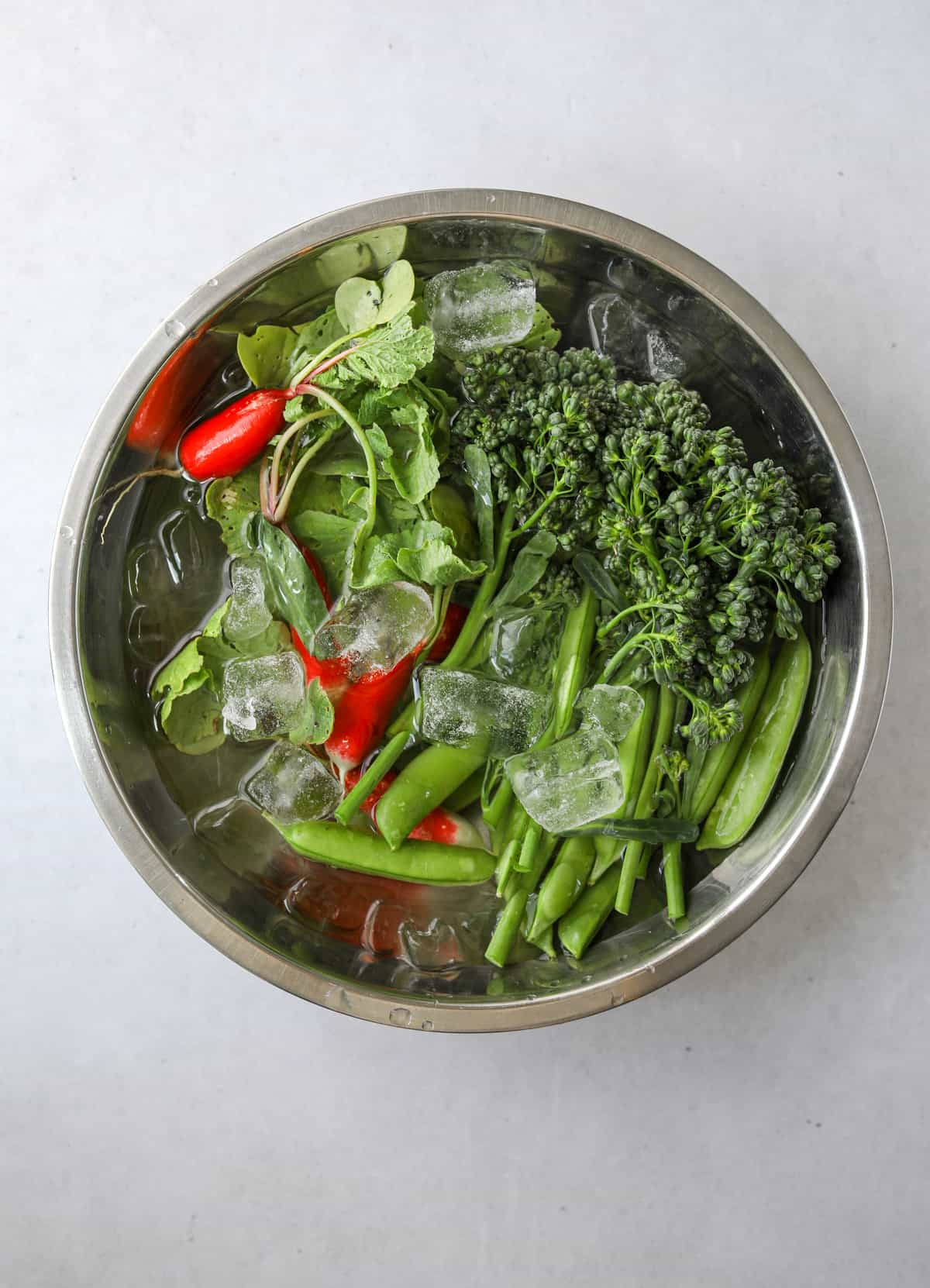 a stainless steel mixing bowl filled with ice water, broccolini, snap peas and radish