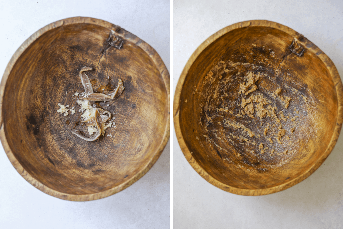 two wooden salad bowls with mashed anchovy and garlic for caesar salad