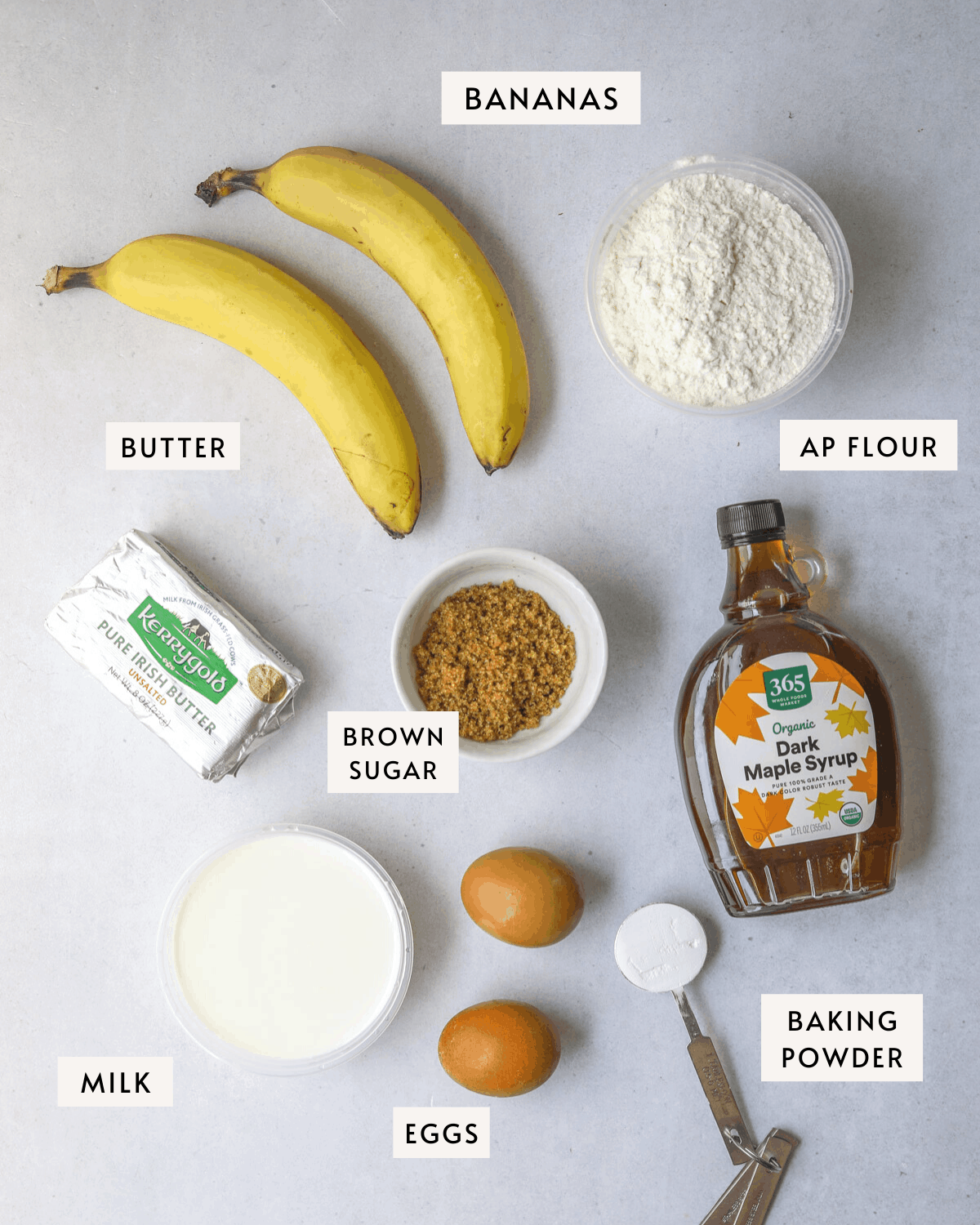 Recipe ingredients on a blue background; two bananas, brown sugar, eggs, maple syrup, butter, milk