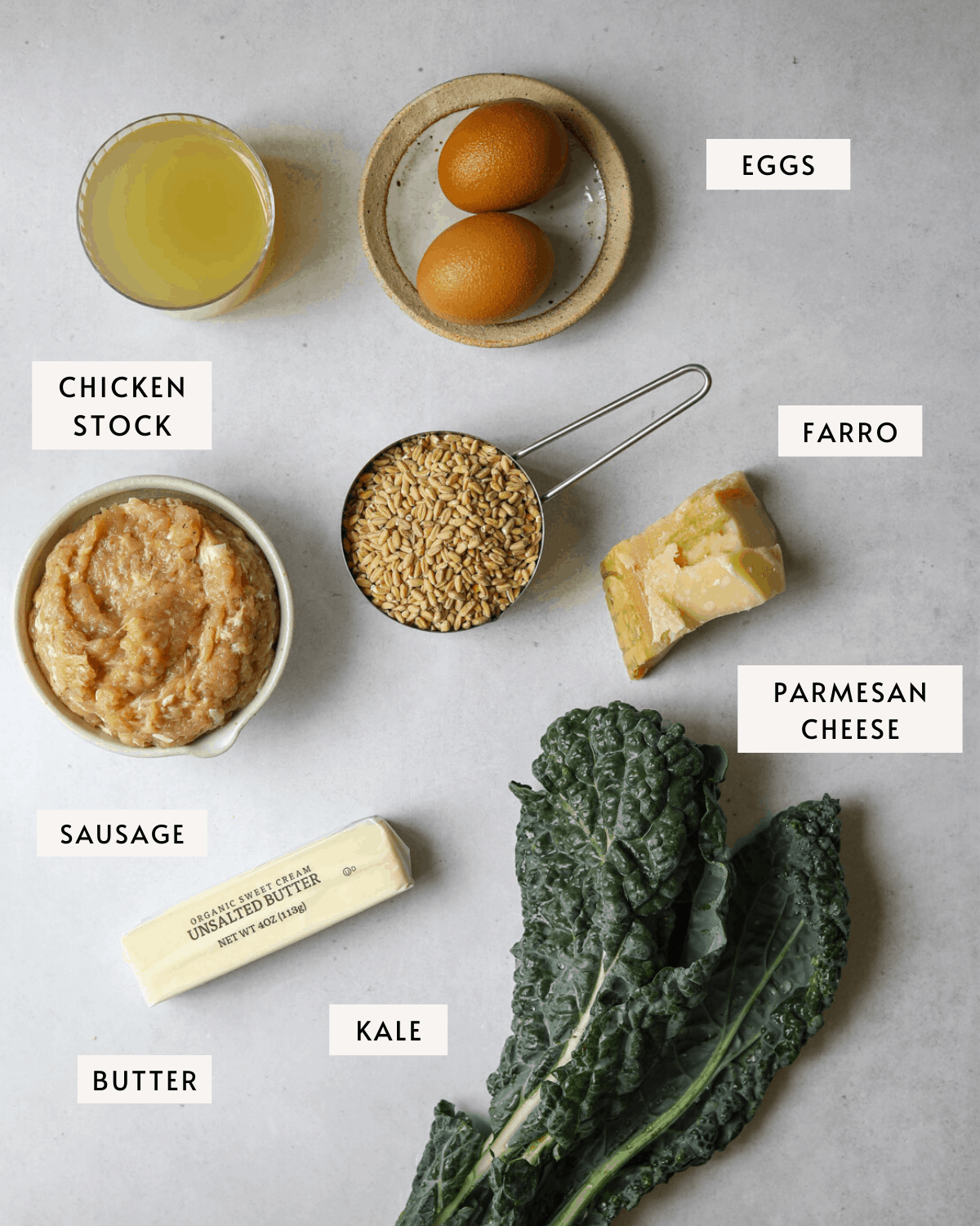 recipe ingredients individually portioned; kale, eggs, farro, parmesan cheese, sausage and butter