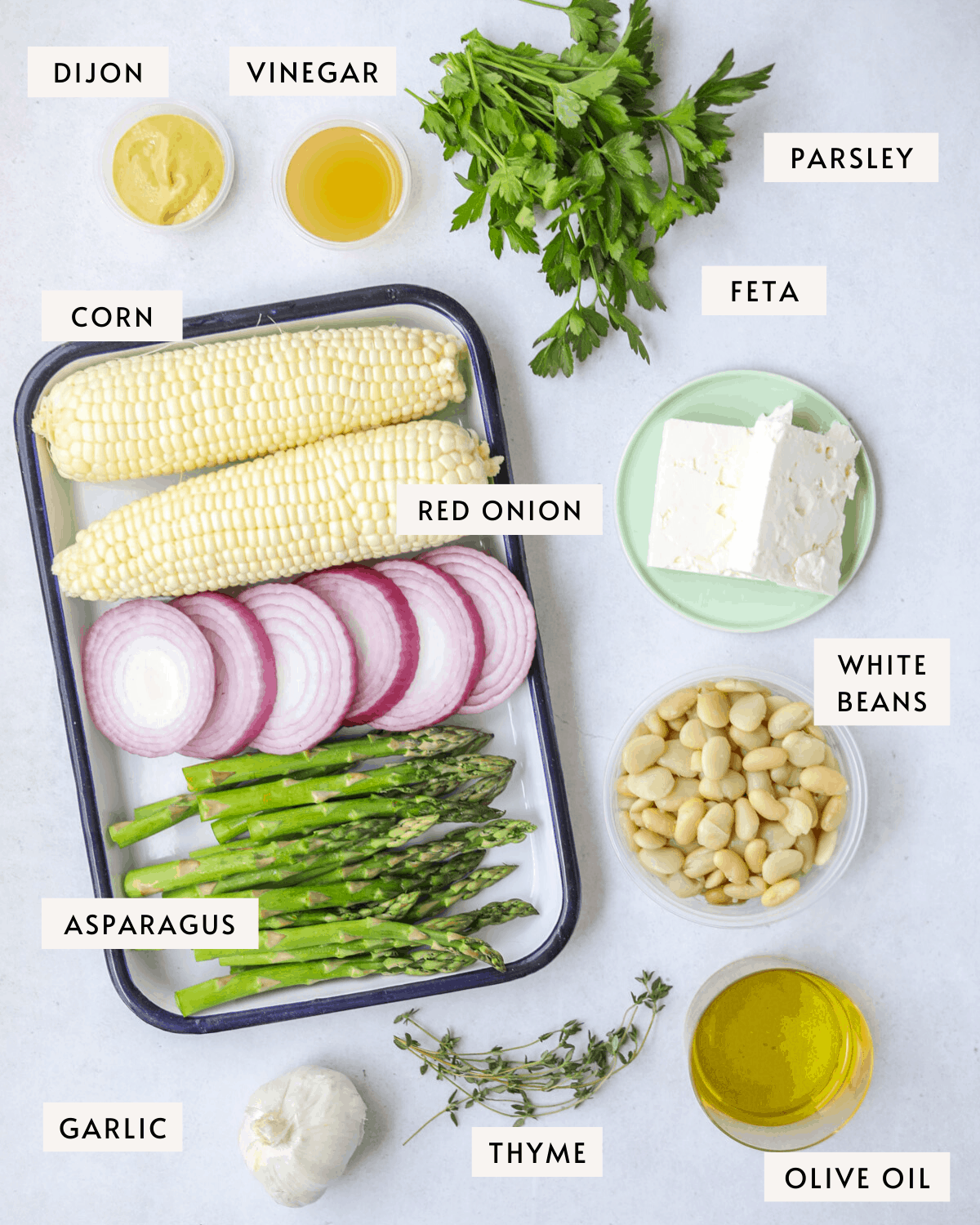 recipe ingredients individually portioned: a platter of corn, sliced red onion and asparagus, a cup of white beans, feta cheese, olive oil, garlic, thyme, parsley etc.