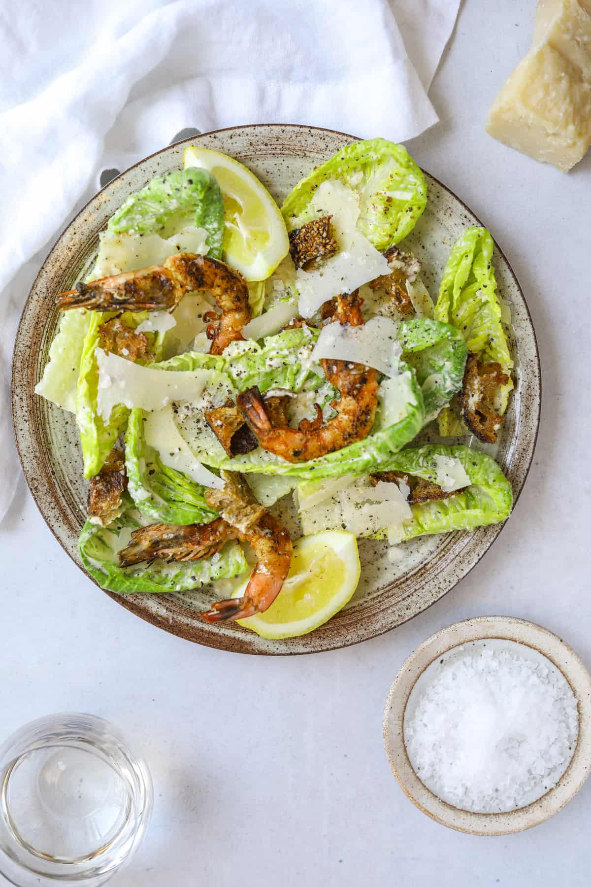 a plate with homemade caesar salad topped with grilled shrimp and shaved parmesan cheese