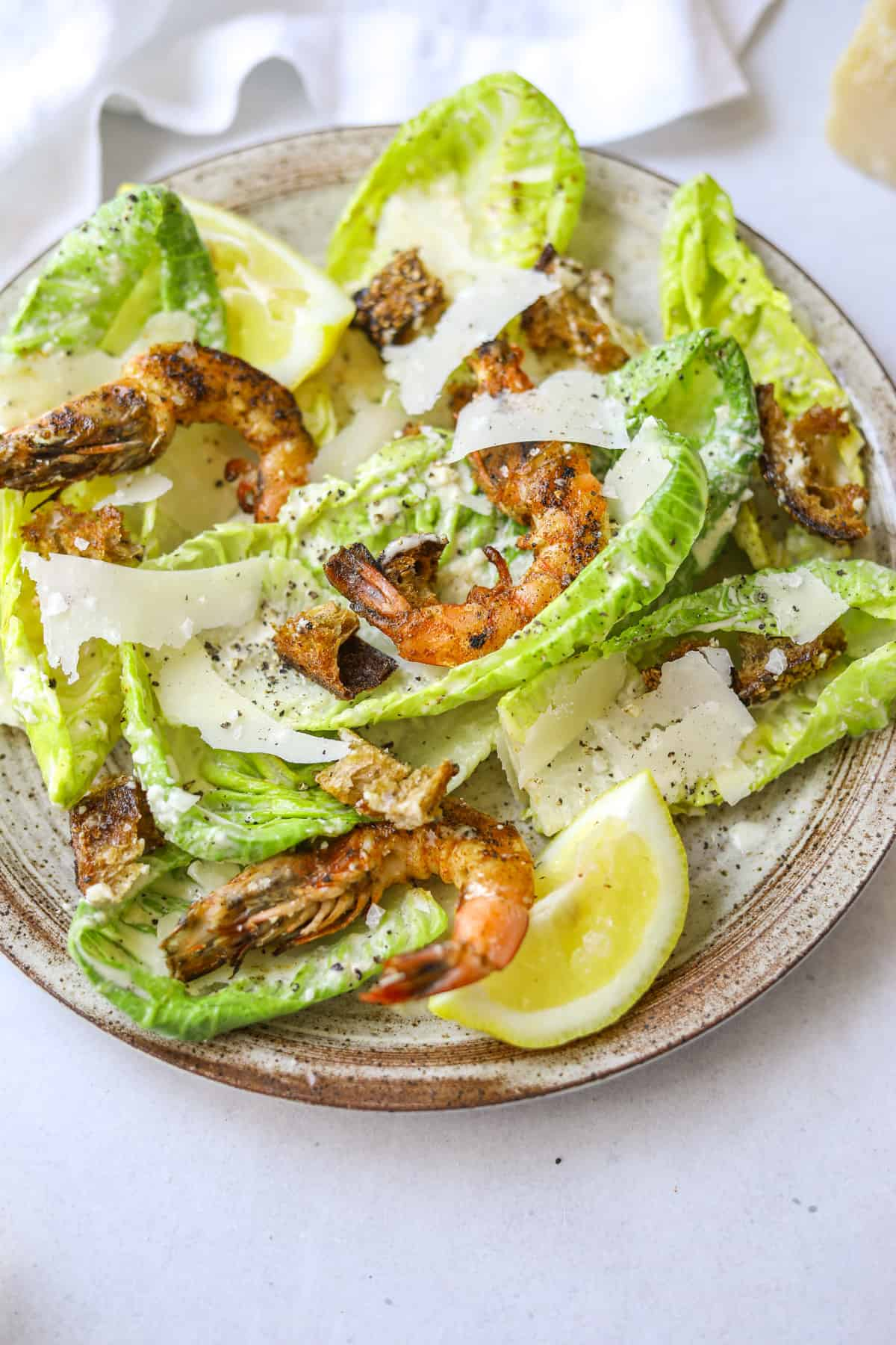 a close up image of grilled shrimp caesar salad with shaved parmesan cheese and a lemon wedge on a speckled ceramic plate