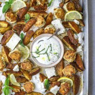 A sheet pan with chicken meat balls, potato wedges and a bowl of garlic feta yogurt