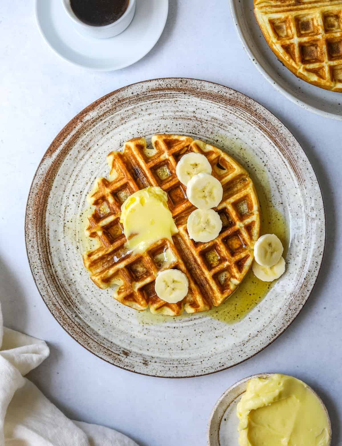 a ceramic plate with a waffle topped with banana slices, a cup of coffee and a dish of butter