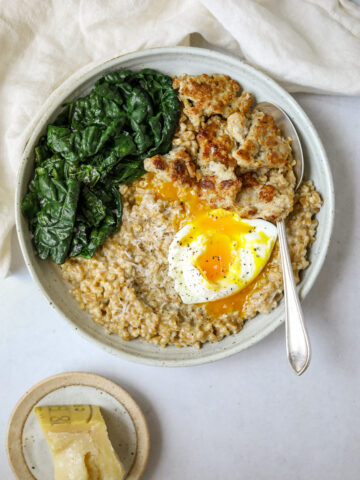 a bowl of savory farro breakfast porridge with a silver spoon and a white linen napkin