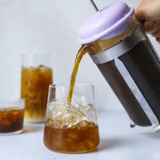 a french press pouring cold brew iced coffee into a clear glass of ice