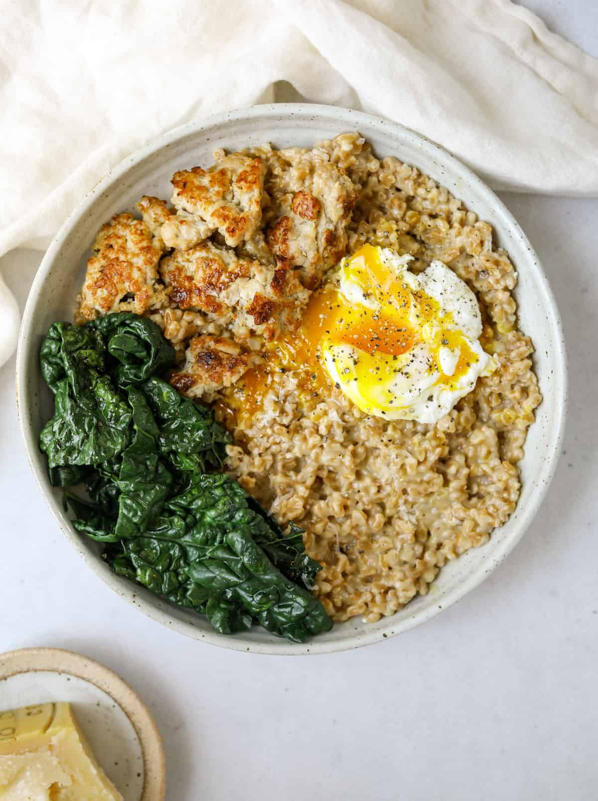 a bowl of savory farro porridge with a poached egg, kale and sausage