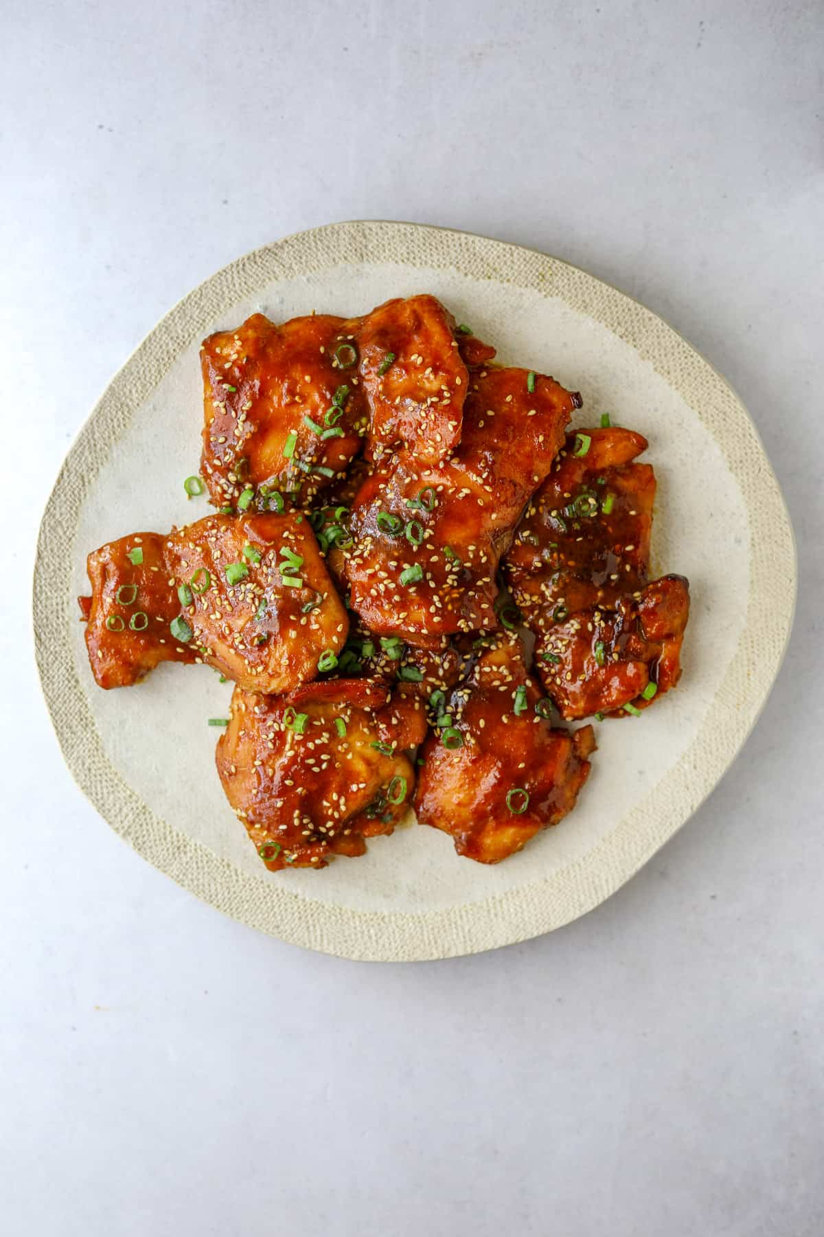 Stick Chicken on a white plate topped with scallions and sesame seeds