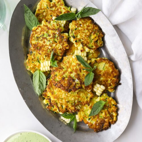 an oval tray filled with corn and zucchini fritters with basil