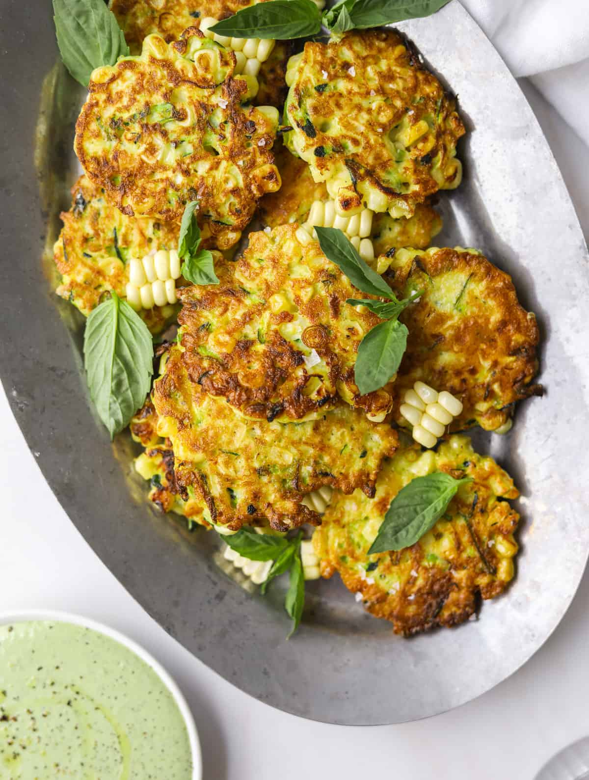 a close up image of corn and zucchini fritters on a silver tray