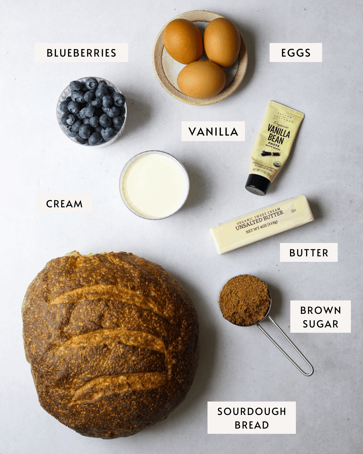 recipe ingredients: a loaf of sour dough bread, vanilla, eggs, blueberries, cream and brown sugar